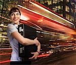 Woman holding briefcase with lights streaking behind Stock Photo - Premium Royalty-Freenull, Code: 635-02152670