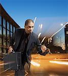 Businessman holding briefcase with light streaking around him Stock Photo - Premium Royalty-Freenull, Code: 635-02152672