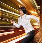 Businesswoman running with lights streaking behind Stock Photo - Premium Royalty-Free, Artist: Blend Images             , Code: 635-02152674