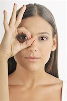Female young adult;looking through fingers' hole Stock Photo - Premium Royalty-Freenull, Code: 644-02152713