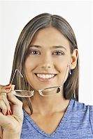 Female young adult removing eyeglasses Stock Photo - Premium Royalty-Freenull, Code: 644-02152912