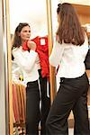 Woman Looking at Herself in Mirror at Clothing Store