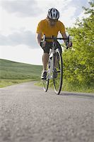 forward - Front view of a man cycling on road Stock Photo - Premium Royalty-Freenull, Code: 622-02198580