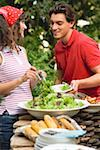 Young woman serving green salad at a barbecue Stock Photo - Premium Royalty-Free, Artist: Kevin Dodge, Code: 659-02211844