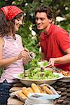 Young woman serving green salad at a barbecue Stock Photo - Premium Royalty-Free, Artist: Kevin Dodge, Code: 659-02211845