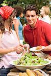 Young woman serving green salad at a barbecue Stock Photo - Premium Royalty-Free, Artist: Kevin Dodge, Code: 659-02211846