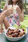 Grilled chicken wings with salad, young people in background Stock Photo - Premium Royalty-Free, Artist: Kevin Dodge, Code: 659-02211965