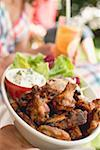Hands holding chicken wings with salad, people in background Stock Photo - Premium Royalty-Free, Artist: Kevin Dodge, Code: 659-02211996