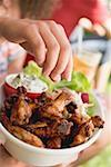 Hand reaching for grilled chicken wings Stock Photo - Premium Royalty-Free, Artist: Kevin Dodge, Code: 659-02211997