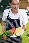 Young man in apron holding vegetables & beer at a barbecue Stock Photo - Premium Royalty-Free, Artist: Kevin Dodge, Code: 659-02212063
