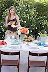 Woman with jug of iced tea by table laid in garden Stock Photo - Premium Royalty-Free, Artist: Westend61, Code: 659-02212644