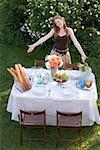 Woman presenting table laid in garden Stock Photo - Premium Royalty-Free, Artist: Aurora Photos, Code: 659-02212645