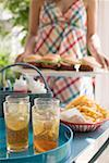 Iced tea and chips on table, woman serving hamburgers Stock Photo - Premium Royalty-Free, Artist: Kevin Dodge, Code: 659-02212668