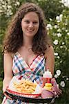 Woman holding tray of chips, ketchup and mustard Stock Photo - Premium Royalty-Free, Artist: Kevin Dodge, Code: 659-02212692
