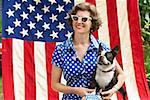 Patriotic woman and Boston Terrier dog posing with American flag Stock Photo - Premium Royalty-Free, Artist: Blend Images, Code: 673-02216548