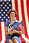 Patriotic woman and Boston Terrier dog posing with American flag Stock Photo - Premium Royalty-Free, Artist: RAW FILE, Code: 673-02216553
