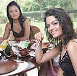 Two young women sitting in a restaurant and smiling Stock Photo - Premium Royalty-Free, Artist: Aluma Images, Code: 630-02219343