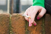 Hand of a girl with cigarette Stock Photo - Premium Royalty-Freenull, Code: 614-02243663