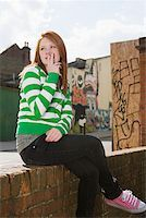Girl sitting on wall and smoking Stock Photo - Premium Royalty-Freenull, Code: 614-02243670