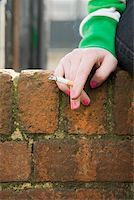 Hand of a girl with cigarette Stock Photo - Premium Royalty-Freenull, Code: 614-02243752
