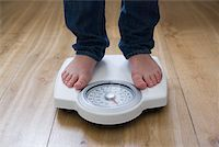 Person standing on scales Stock Photo - Premium Royalty-Freenull, Code: 614-02244174
