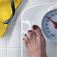 Woman Standing on Scale, Crossing Toes For Luck    Stock Photo - Premium Rights-Managednull, Code: 700-02245705