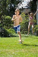 Two children playing in a sprinkler Stock Photo - Premium Royalty-Freenull, Code: 653-02261018