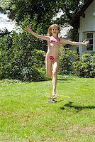 A girl running through a sprinkler Stock Photo - Premium Royalty-Freenull, Code: 653-02261040