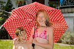 Two children standing under an umbrella and getting hit by spraying water Stock Photo - Premium Royalty-Free, Artist: Elizabeth Knox, Code: 653-02261043