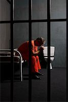 A prisoner sitting on a bed in a prison cell Stock Photo - Premium Royalty-Freenull, Code: 653-02261091