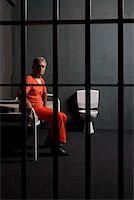 Prisoner sitting on a bed in a prison cell Stock Photo - Premium Royalty-Freenull, Code: 653-02261093