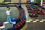 High angle view of go-cart racer at starting line with a man waving a flag Stock Photo - Premium Royalty-Free, Artist: Transtock, Code: 625-02266458