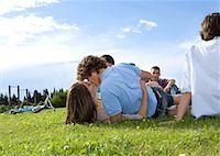 Teen lovers kissing in front of friends Stock Photo - Premium Royalty-Freenull, Code: 649-02290314