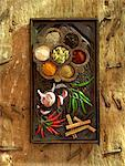 Spices on wood including chillis, garlic,cinnamon,cardomom seeds,ground ginger. Stock Photo - Premium Rights-Managed, Artist: foodanddrinkphotos, Code: 824-02294074