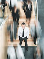 Calm businessman standing in busy office Stock Photo - Premium Royalty-Freenull, Code: 635-02312491