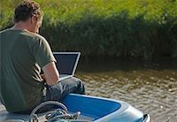 Back view of a man sitting on a boat using a laptop computer    Stock Photo - Premium Rights-Managednull, Code: 822-02315685