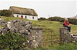 Woman Sitting on Gate in Front of Traditional Thatched Cottage in Inishmor, Aran Islands, County Galway, Ireland
