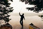 Boy Fishing Off Dock Early in the Morning, Algonquin Park, Ontario, Canada
