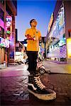 Boy Standing on Sculpture of Shoe, Myeong-dong Shopping Area, Seoul, South Korea    Stock Photo - Premium Rights-Managed, Artist: R. Ian Lloyd, Code: 700-02370967