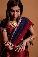 singapore traditional costume lady - Indian woman painting hand with henna Stock Photo - Premium Royalty-Freenull, Code: 655-02375864