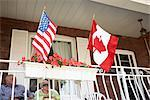 Senior Couple on Front Porch with American and Canadian Flags