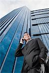 Low angle view of a businessman talking on a mobile phone and smiling    Stock Photo - Premium Rights-Managed, Artist: Glowimages, Code: 837-02378903