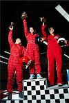 Low angle view of a three female go-carts racers standing on winners podium with their trophies    Stock Photo - Premium Rights-Managed, Artist: Glowimages, Code: 837-02379472