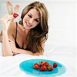 Portrait of a young woman eating a strawberry    Stock Photo - Premium Rights-Managed, Artist: Glowimages, Code: 837-02379486