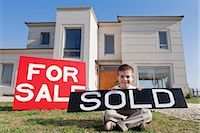 sold sign - Portrait of a boy holding a sold signboard and smiling    Stock Photo - Premium Rights-Managednull, Code: 837-02380866