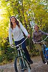 Two Women Riding Bicycles through Forest