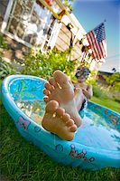 Boy wearing snorkel and lying in a wading pool Stock Photo - Premium Royalty-Freenull, Code: 673-02386684