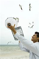 release - Man releasing bird at the beach, emZSy bird cage in hands Stock Photo - Premium Royalty-Freenull, Code: 633-02417926