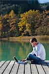 Man Sitting on Dock, Talking on Cell Phone and Using Laptop, Fuschlsee, Fuschl am See, Salzburger Land, Austria    Stock Photo - Premium Rights-Managed, Artist: Bettina Salomon, Code: 700-02428742