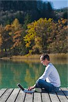 Man Sitting on Dock, Using Laptop, Fuschlee, Fuschl am See, Salzkammergut, Salzburger Land, Austria    Stock Photo - Premium Rights-Managednull, Code: 700-02428743